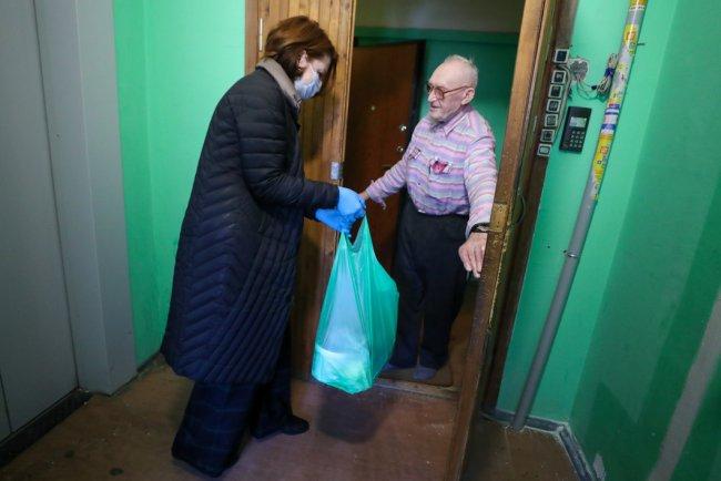 Волонтер благотворительного фонда во время доставки продуктов одиноким пожилым людям. Фото: Александр Демьянчук / ТАСС