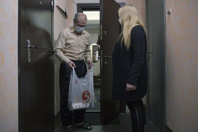 Волонтер вручает продуктовый набор пенсионеру в Санкт-Петербурге. Фото: РИА Новости