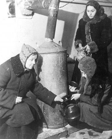 Жители Смольнинского района в бомбоубежище набирают горячую воду, 1942 год. Фото: Давид Трахтенберг