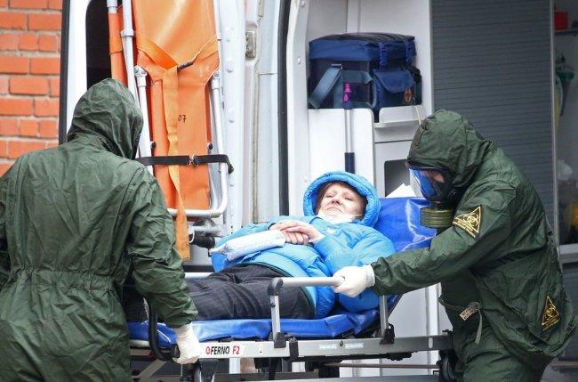 Сотрудники скорой помощи и пациентка у приемного отделения Покровской больницы. Фото: Петр Ковалев / ТАСС